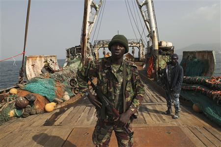 Sierra Leonean security forces guard the Marampa 803, a vessel apprehended for alleged illegal fishing activities, that has been moored off the West African country's capital Freetown January 21, 2012. West Africa, recognized as one of the world's richest fisheries grounds teeming with snapper, grouper, sardines, mackerel and shrimp, loses up to $1.5 billion worth of fish each year to vessels fishing in protected zones or without proper equipment or licenses. Widespread corruption and a continuing lack of resources for enforcement mean huge foreign trawlers often venture into areas near the coast that are reserved exclusively for artisanal fishermen, allowing them to drag off tonnes of catch and putting at risk the livelihoods of millions of local people. Picture taken January 21, 2012. To match Feature WESTAFRICA-FISHING/ REUTERS/Simon Akam