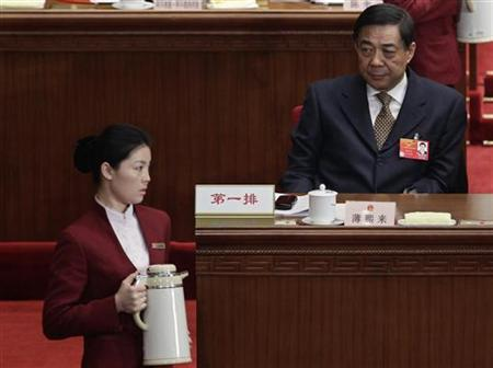 China's Chongqing Municipality Communist Party Secretary Bo Xilai looks at a tea attendant as she walks past in front of him during the opening ceremony of National People's Congress (NPC) at the Great Hall of the People in Beijing March 5, 2012. REUTERS/Jason Lee