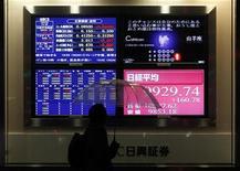 Человек идет мимо электронных табло в Токио, 9 марта 2012 г. Фондовые рынки Азии снизились в четверг из-за новых опасений по поводу темпов роста китайской экономики, но улучшение общей экономической перспективы поддержало аппетит инвесторов к риску. REUTERS/Issei Kato