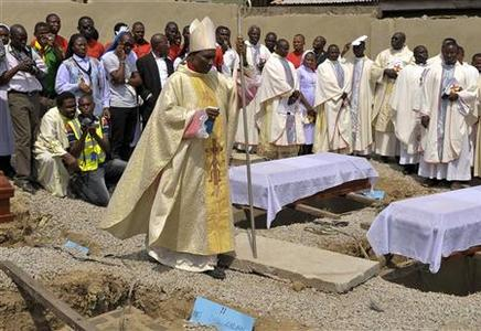 Clergymen gather around the coffins of the victims of the Christmas day bombing at St Theresa Catholic Church Madalla, during a mass funeral for the victims, outside Nigeria's capital Abuja February 1, 2012. REUTERS/Afolabi Sotunde