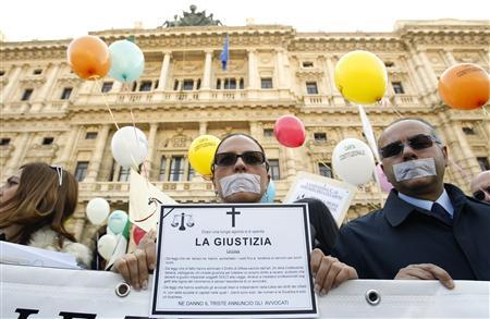 A lawyer holds a sign titled:' The justice is killed' during a protest in front of the Justice Palace in Rome March 15, 2012. REUTERS/Alessandro Garofalo