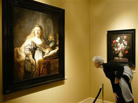 A visitor admires the painting 'Minerva in Her Study', by Dutch painter Rembrandt van Rijn, which is for sale at the annual TEFAF art fair in Maastricht, March 8, 2002. REUTERS/Michael Kooren
