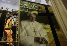 <p>Un hombre se para junto a un póster del Papa Benedicto XVI durante la procesión del vía crucis en La Habana, mar 10 2012. Cuba fomenta la educación religiosa antes de la visita a la isla del Papa Benedicto XVI y tras medio siglo de ausencia en la formación, dijo un obispo de la Iglesia Católica, quien también celebró la apertura de las publicaciones oficiales a temas relativos a la fe, algo vedado en el pasado. REUTERS/Stringer</p>