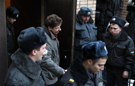 Entrepreneur Alexei Kozlov (2nd L, back) is escorted after a court session in Moscow March 15, 2012. REUTERS/Anton Golubev