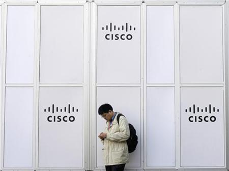 A man looks at his mobile next to a Cisco banner at the Mobile World Congress in Barcelona February 17, 2010. REUTERS/Albert Gea