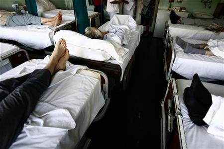 People are seen on beds in a room at the National Cancer Research Center within the Institute for Oncology and Radiology in Belgrade, October 6, 2009. REUTERS/Djordje Kojadinovic