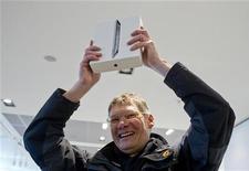 """Первый покупатель нового iPad в магазине электроники в Берлине, 16 марта 2012 г. Последний iPad от Apple претендует на роль нового бестселлера, поскольку сотни поклонников """"яблочной"""" продукции из самых разных стран столпились в пятницу у дверей магазинов компании по всей Азии, желая стать первыми счастливыми обладателями гаджета. REUTERS/Thomas Peter"""