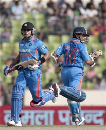 Sachin Tendulkar (R) and Virat Kohli run between the wickets against Bangladesh during their One Day International (ODI) cricket match of Asia Cup in Dhaka March 16, 2012. REUTERS/Andrew Biraj