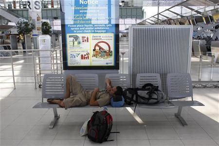 A passenger takes a rest in the departure area at Bangkok's Suvarnabhumi Airport December 4, 2008.  REUTERS/Darren Whiteside (THAILAND)