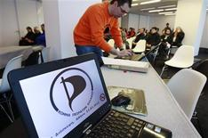 Spokesman of the Pirates party Anestis Samourkasidis, 42, works behind a laptop screen displaying a logo of the party during its first gathering in a hotel in Athens March 11, 2012. REUTERS/John Kolesidis