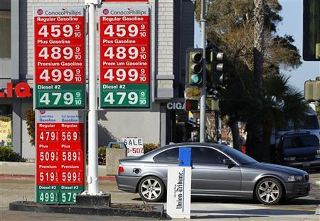 A commuter drives past a gas station signage displaying current prices for self serve and full serve gasoline in La Jolla, California March 8, 2012. REUTERS/ Mike Blake