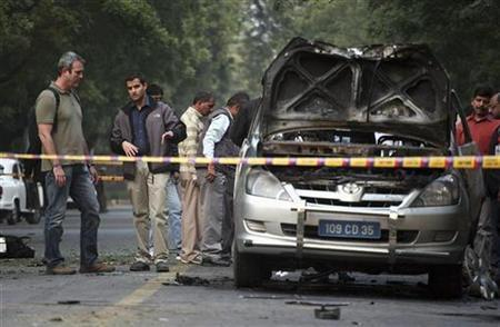 People examine a damaged Israeli embassy car after an explosion in New Delhi February 13, 2012. REUTERS/Parivartan Sharma/Files