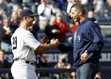 Former New York Yankees pitcher Andy Pettitte (R) shakes hands with New York Yankees designated hitter Jorge Posada after throwing the ceremonial first pitch before Game 2 of the MLB American League Division Series baseball playoffs between the New York Yankees and Detroit Tigers at Yankee Stadium in New York, October 2, 2011. REUTERS/Mike Segar