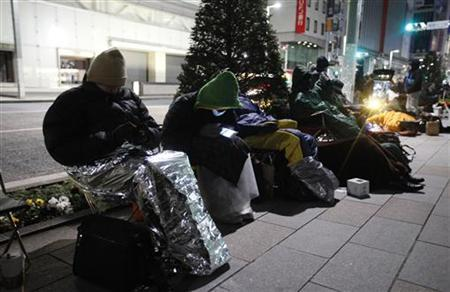 People sit on a street in front of an Apple store as they wait for the release of the new iPad in Tokyo March 16, 2012. Apple's new iPad uses chips made by Qualcomm , Broadcom, Samsung Electronics and other semiconductor makers, according to repair firm iFixit, which cracked open one of the devices. REUTERS/Kim Kyung-Hoon