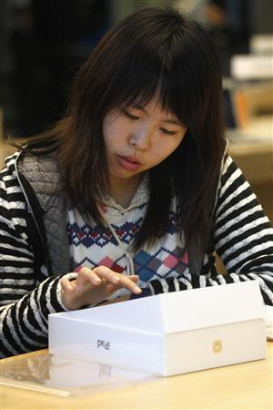 A customer looks at the new iPad at an Apple store in Hong Kong March 16, 2012. The Apple branch in Hong Kong was the first in the region to open for online orders to avoid queuing confusion. REUTERS/Tyrone Siu