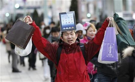 A man wearing a cardboard hat depicting Apple's new iPad reacts as he walks to purchase the tablet in front of the Apple Store Ginza in Tokyo March 16, 2012. Apple's new iPad went on a sale in Japan on Friday and more than 450 people waited on the line to purchase the new device in front of the shop prior to its opening. REUTERS/Kim Kyung-Hoon