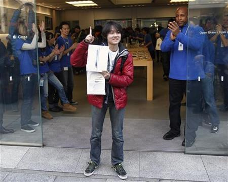 Japan's first new iPad buyer Ryu Watanabe poses after purchasing the tablet in front of the Apple Store Ginza in Tokyo March 16, 2012. Apple's new iPad went on a sale in Japan on Friday and more than 450 people had waited on the line to purchase the new device in front of the shop prior to its opening. Ryu had waited for the sale on the street since Wednesday. REUTERS/Kim Kyung-Hoon
