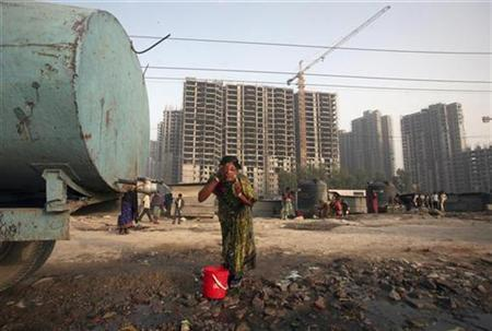 A labourer washes her face from a water tanker in front of residential apartments undergoing construction in Noida on the outskirts of New Delhi March 16. 2012. REUTERS/Parivartan Sharma