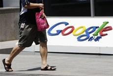 Um empregado caminha ao lado do logotipo do Google em frente à sua antiga sede, em Pequim, 2 de junho de 2011. A Comissão de Comércio Federal dos EUA está analisando se o Google enganou os consumidores ao plantar os chamados cookies de Internet no navegador da Apple sem o consentimento dos usuários, informou a Bloomberg na sexta-feira citando fontes. REUTERS/Jason Lee
