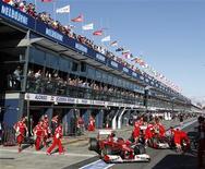 Os pilotos de Fórmula Um Fernando Alonso (esquerda) da Espanha e Felipe Massa do Brasil são empurrados de volta para suas garagens durante os treinos do Australian F1 Grand prix no circuito de Albert Park em Melbourne, 17 de março de 2012. REUTERS/Brandon Malone