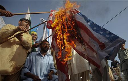 Supporters of Shabab-e-Milli, the youth wing of the Jamaat-e-Islami party burn the U.S. flag during an anti-American demonstration in Karachi on March 16, 2012. REUTERS/Athar Hussain