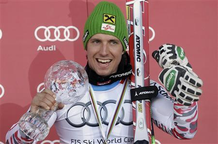 Austria's Marcel Hirscher reacts with a trophy for the men's giant slalom event at the podium at the alpine ski World Cup finals in Schladming March 17, 2012. REUTERS/Leonhard Foeger