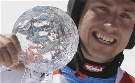 Austria's Marcel Hirscher reacts with a trophy in the finish area during the men's Giant Slalom at the alpine ski World Cup finals in Schladming March 17, 2012. REUTERS/Leonhard Foeger