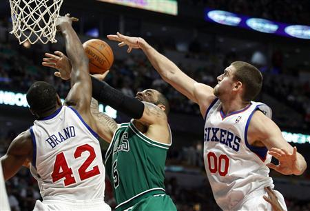 Philadelphia 76ers' power forward Elton Brand (42) and Spencer Hawes (00) block Chicago Bulls' power forward Carlos Boozer's (5) shot during the second half of their NBA basketball game in Chicago March 17, 2012. The Bulls won 89-80. REUTERS/Jeff Haynes