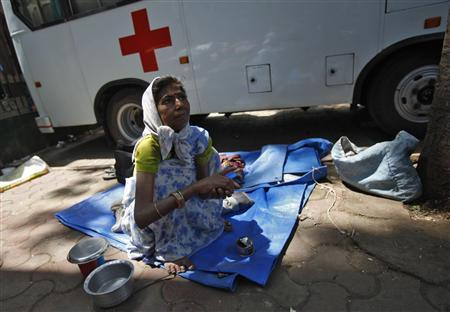A woman with cancer sits on a pavement outside the Tata Memorial Hospital in Mumbai March 15, 2012. A ruling this week that for the first time allowed an Indian drugmaker to make and sell a blockbuster cancer drug at a fraction of the market price has been hailed as a breakthrough by campaigners for cheaper medicine in the emerging economy. Photo taken March 15, 2012. REUTERS/Vivek Prakash