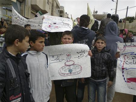 Demonstrators protest against Syria's President Bashar al-Assad near Idlib March 16, 2012. The banner reads ''Idlib will never kneel''. REUTERS/Shaam News Network/Handout