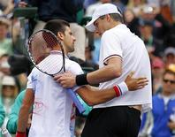 Novak Djokovic, da Sérvia (esquerda) cumprimenta John Isner, dos Estados Unidos, após Isner ter ganhado um tie-break do terceiro set para vencer a semi-final masculina no torneio de torneio de Indian Wells, California, 17 de março de 2012. REUTERS/Mike Blake