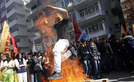 A demonstrator jumps over a bonfire during a gathering to celebrate Newroz in Ankara March 18, 2012. REUTERS/Umit Bektas