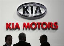 Visitors talk on the KIA Motors booth during the second media day of the 82nd Geneva Car Show at the Palexpo Arena in Geneva March 7, 2012.REUTERS/Denis Balibouse