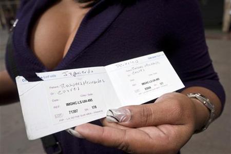 3月18日、仏企業ポリ・アンプラン・プロテーズ製の欠陥豊胸材をめぐり、ベネズエラでは無償交換ができない場合、女性約2000人が医師やクリニック、販売業者を相手取って訴訟を起こす可能性が出ている。写真はポリ・アンプラン・プロテーズ製豊胸材による手術を受けた証明書を見せる女性。1月撮影(2012年 ロイター)