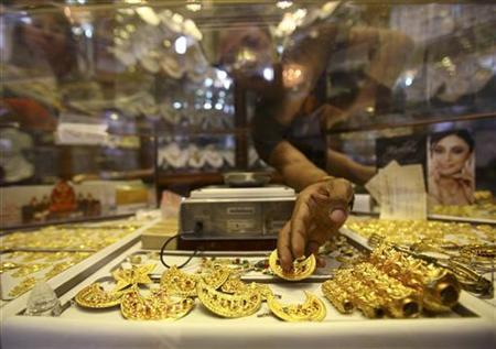 The hand of a Nepalese jewelry store keeper is seen as she arranges gold jewelry in Kathmandu August 8, 2011. REUTERS/Navesh Chitrakar/Files