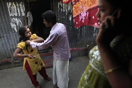 Seventeen-year-old prostitute Hashi (L) deals with a customer as Maya (R) waits to get one at Kandapara brothel in Tangail, a northeastern city of Bangladesh, March 5, 2012. REUTERS/Andrew Biraj