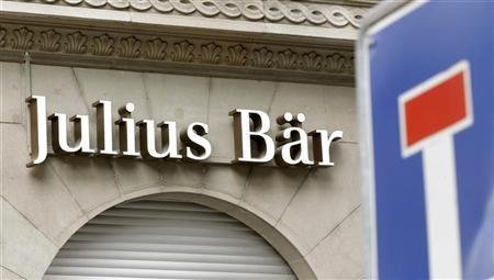A traffic sign is pictured in front of the logo of Swiss bank Julius Baer in Zurich February 6, 2012. REUTERS/Arnd Wiegmann