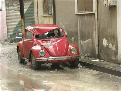 A damaged car is seen in a street in Homs March 16, 2012. REUTERS/Sumar Al Homsi/Shaam News Network/Handout