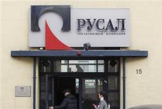"""People enter an office of RUSAL company in Moscow March 19, 2012. RUSAL, the world's top aluminium maker, posted a 92 percent drop in yearly net profit, hit by a write-down in the value of its stake in miner Norilsk Nickel as it grapples with a damaging row over its future between two Russian billionaires. The sign reads """"RUSAL. The management company"""". REUTERS/Denis Sinyakov"""