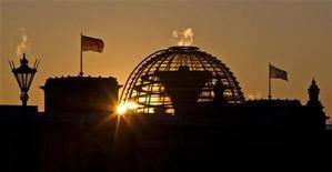 Солнце поднимается за куполом здания Рейхстага в Берлине, 1 февраля 2012 года. Внезапное похолодание вызвало замедление немецкой экономики в феврале, и промышленность пока далека от устойчивого восстановления, сообщил в понедельник Бундесбанк, отметив, что опережающие индикаторы указывают на экономический подъем. REUTERS/Thomas Peter