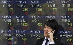A man smiles as he talks on a mobile phone in front of an electronic monitor displaying share prices outside a brokerage in Tokyo March 14, 2012. REUTERS/Yuriko Nakao
