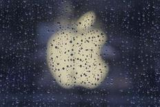 Raindrops are seen in front of an Apple logo outside an Apple store in Shanghai February 22, 2012. REUTERS/Aly Song