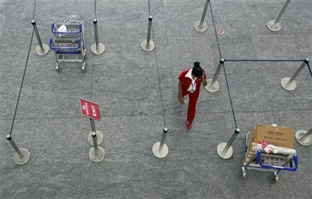 A Kingfisher Airlines staff member walks through their empty check in area at Bengaluru International Airport in Bangalore, March 9, 2012. REUTERS/Vivek Prakash