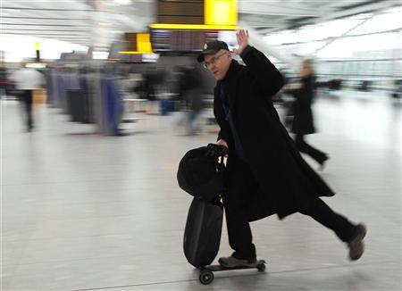 A passenger travels on a scooter with his luggage at Heathrow airport in London March 16, 2012.   REUTERS/Luke MacGregor