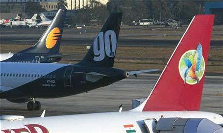 The tailfin of a Kingfisher Airlines aircraft (R) is pictured next to the tailfins of Go Air (C) and Jet Airways aircraft as it waits at a gate before departure from Mumbai's domestic airport February 21, 2012. REUTERS/Vivek Prakash
