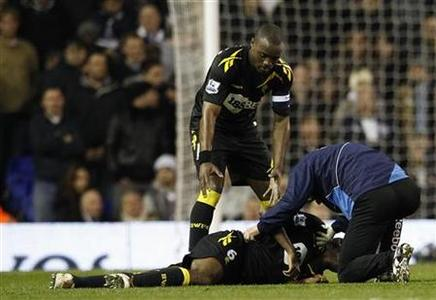 Bolton Wanderers' Nigel Reo-Coker helps a member of the club's medical staff attend to Fabrice Muamba after he collapsed on the pitch during their FA Cup quarter-final soccer match against Tottenham Hotspur at White Hart Lane in London March 17, 2012. REUTERS/Suzanne Plunkett