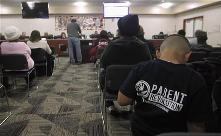 Eight-year-old Abraham Zamarripa sits in the audience in support of Patrick DeTemple, director of NGO Parent Revolution, who is speaking during a Adelanto School District board meeting regarding the parent trigger law, in Adelanto, California March 6, 2012. REUTERS/Alex Gallardo
