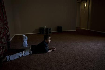 Oscar Avalos, 7, lies in the empty living room of his family's apartment in Stockton, California, March 6, 2012. REUTERS/Max Whittaker