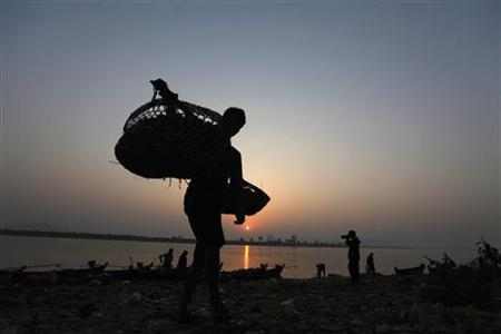 A man unload tomatoes from a small boat along the Irrawaddy river banks to be sold in Myitkyina market in Myanmar's northern Kachin State February 25, 2012. REUTERS/Soe Zeya Tun