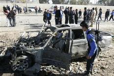Сотрудник службы безопасности Ирака осматривает взорвавшийся в Киркуке автомобиль, 20 марта 2012 года. По меньшей мере 29 человек стали жертвами взрывов бомб в нескольких городах и поселках Ирака в преддверии саммита Лиги арабских государств, который должен пройти на следующей неделе в Багдаде. REUTERS/Ako Rasheed